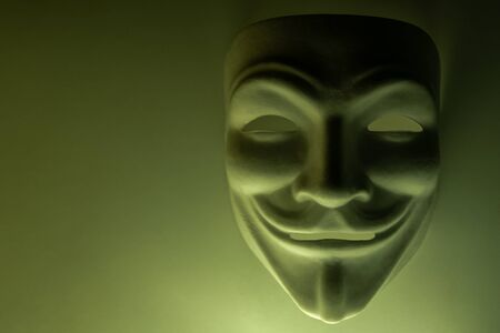 A mask that looks like a symbol of a group of hackers Anonymous. Tinted in olive color. Close-up. Shooting a subject in a dark key. Background for screensaver or desktop wallpaper monitor. Copy space.