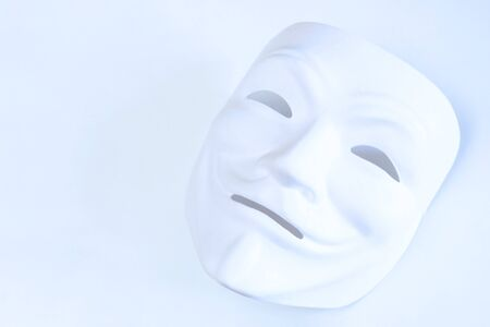 White mask on a white background. The symbol of an anonymous hacker. Shooting in a light manner. The effect of film grain. Copy space. Stockfoto