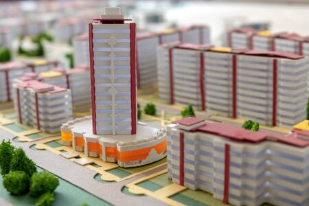 Layout of high-rise buildings and streets in an abstract city. Background to illustrate mortgage lending and new home construction. Toning, macro photography, shallow depth of field. Project of modern houses.