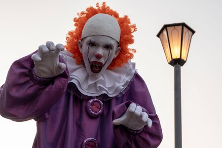 The face is a very scary clown with red hair and sharp teeth close-up. A teenage boy in an IT suit opened his mouth next to a street lamp. Cosplay for carnival or for halloween. Selective focus.