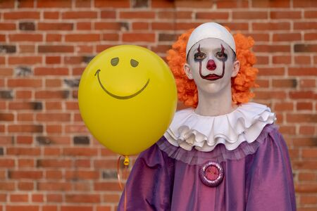 Cosplay: A guy dressed as an evil scary clown similar to Pennywise. A young man as IT against a brick wall with a yellow ball in his hands with a painted smile. Copy space.