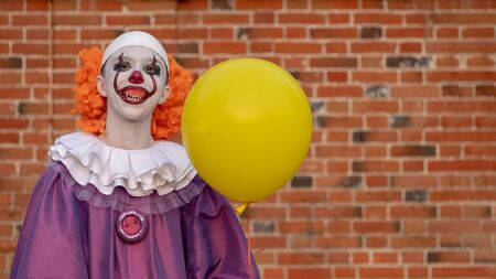 A teenage boy in a scary clown costume with teeth smiles funny against a red brick wall. Street makeup on the face of a teenager. Yellow balloon.Celebrating Halloween or All Saints Day. Copy space.
