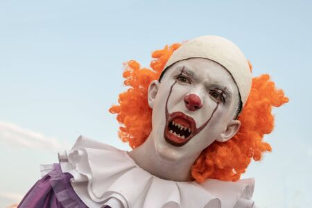 Portrait of a guy in the image of a clown with sharp teeth on a background of blue sky. Carnival costume for halloween or all saints day. Street makeup on the face of a teenager.