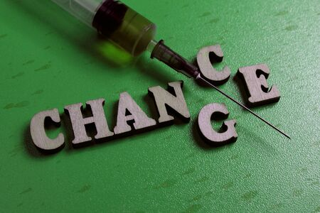 Chance or change. Syringe needle with brown liquid and the inscription made of wooden letters. Dark green background. The concept of choice, drug addiction, medical error.