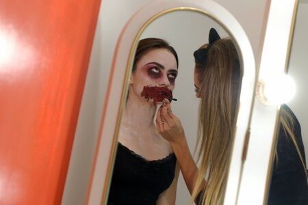 The process of applying scary makeup to celebrate Halloween. The reflection in the mirror as a girl puts bloody make-up on the face of another girl. Red background. Copy space. Bodypainting.