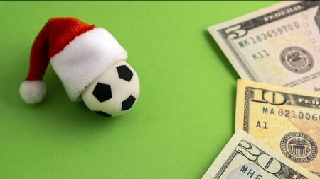 Soccer ball in santa claus hat next to small us dollar bills on a green background. The concept of sports betting in the new year, gifts and cash incentives for football players, corruption and approval of financial estimates . Five, ten, twenty dollars blurry. Copy space.