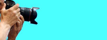 Cámara réflex digital en manos de un anciano sobre un fondo azul. Primer plano, espacio de copia, lugar para textos. Plantilla para el diseño de un banner publicitario. Un periodista fotógrafo profesional con experiencia. Foto de archivo