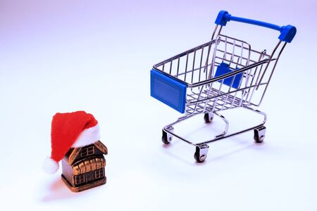Shopping cart and souvenir house with santa claus hat. Concept New Year's discounts, Christmas surprise, housewarming or buying a new home. Copy spase. Banco de Imagens
