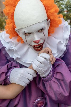 A guy in a scary clown costume with sharp teeth holds someone else's hand and pretends to want to bite her off. Vertical frame. Cosplay to celebrate Halloween, All Saints Day or Carnival.