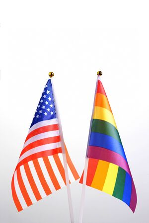 USA and LGBT. Two table flags on a white background. The concept of a meeting of American people with representatives of non-traditional sexual orientation. Copy space.