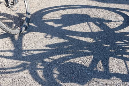 Shadow and wheel of a bicycle on the pavement. Abstract background. The concept and promotion of a healthy lifestyle among the population. Sports event bike ride. Cycling.
