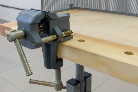 Vise attached to the workbench. Workplace of a carpenter. School or home workshop. Close-up. Imagens