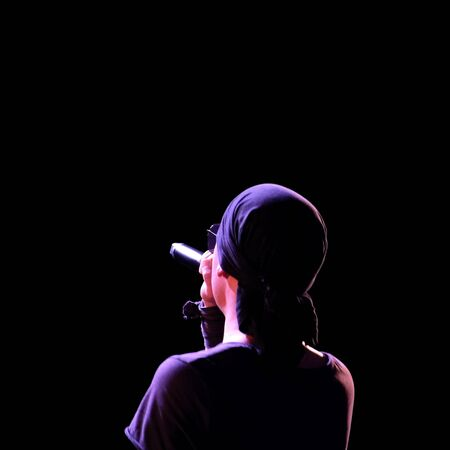 Silhouette of a rock singer in dark clothes and a bandana on a black background. Image of an abstract guy with a microphone in his right hand. The view from the back. Square frame. Isolated. Copy space.