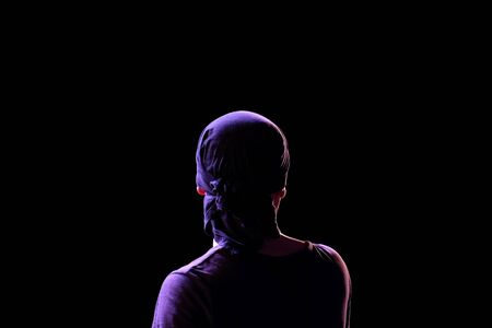 Silhouette of a guy in a dark T-shirt and bandana in back modeling light on a black background. View of a man from the back. Copy space. Isolated.