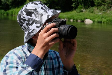 A young man in a shirt and hat looks through the peephole of a molten SLR camera. Strange photographer in nature. The tropical heat ruined the camera.