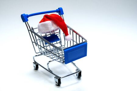 Santa Claus hat on a shopping trolley on a white background. Christmas and New Year discount concept, online, consumer basket level, black friday and holiday sale.