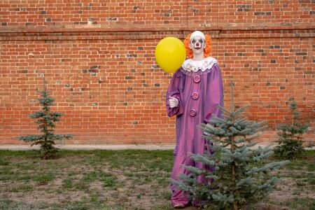 A guy in a clown or mime costume with a yellow ball near a small green Christmas tree against a brick wall for All Saints Day holiday. Street cosplay for halloween, carnival or party.