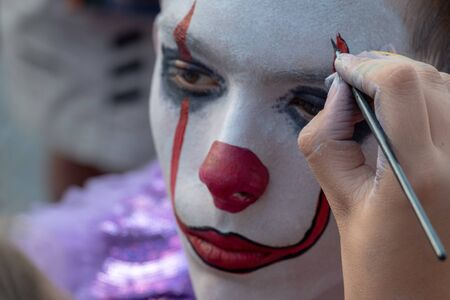 Female hand holds a brush and paints the face of a teenager. The image of a clown or mime for the holiday of All Saints Day or Halloween. Body painting or street makeup. Preparing for a carnival party.