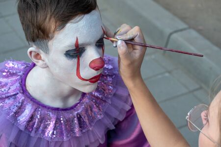 Body painting or street makeup. Female hand holds a brush and paints the face of a teenager. The image of a clown or mime for the holiday of All Saints Day or Halloween. Preparing for a carnival or party.