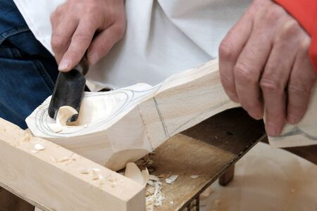 Making a wooden spoon. Traditional handicraft woodworking or hobby. Mens hands with a tool closeup. Stock fotó