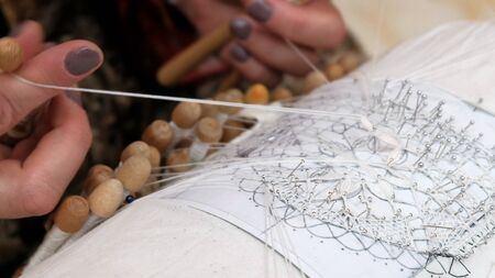 Close-up of female hands fingering coils between fingers. Hand Weaving Lace craft. The craftswoman spins a beautiful pattern from thin silk threads. The ancient tradition of the lace pillow.