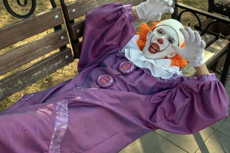 A clown with sharp teeth lies on a bench in a city park. Halloween or Carnival Cosplay for All Saints Day. The concept of fear and horror. Imagens