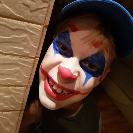 A cheerful boy with a clown mask painted on his face peeks around the corner. Body painting and makeup for a school carnival or halloween celebration. Square, dynamic blockage of the horizon.
