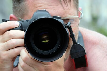 Camera instead of the eyes. An adult man in glasses without clothes photographs the nature of an abstract digital SLR camera. Professional photographer traveler. Imagens