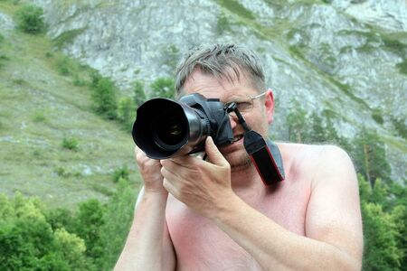 A professional photographer without clothes is looking into the viewfinder of a digital SLR camera. Traveler or vacationer. Adult man in glasses takes pictures of nature in the mountains.