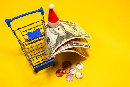 Jackson in Santas hat. One, five, and twenty US dollars in a shopping basket. Metal coins cents on a yellow background. How much money do Americans spend on Christmas holidays? Copy space.