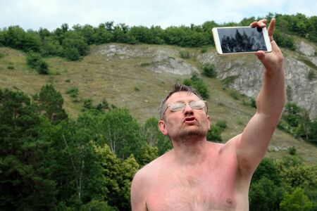 An unshaven middle-aged man takes off taking a selfie against the backdrop of the mountains. Bespectacled photographer without clothes on nature holds the phone in his left hand. Funny face while relaxing, vacation and traveler hobby. Imagens