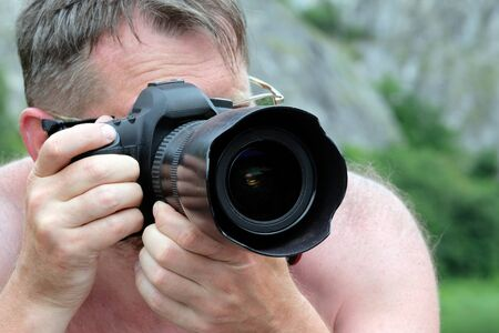Professional photographer traveler. An adult man in glasses without clothes photographs the nature of an abstract digital SLR camera.