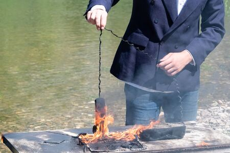 A laptop and a phone burned out on an office desk near the river. The male hand of a freelancer, manager or businessman holds the wire of the telephone receiver on fire. The concept of hated work or insurance case. Loss of digital data or the intentional destruction of electrical appliances. Technical Support Hotline.