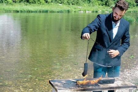 Businessman burned office equipment outdoors during the vacation. The concept of hateful work. Destruction of digital data or non-compliance with safety precautions. A laptop and a phone burned out on a table near the river. The male hand of the manager holds the wire the telephone receiver on fire.