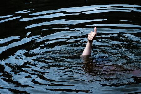 A male hand with a raised finger sticks out of an oil-like fluid. A man is drowning in black water. The concept of excellent quality or low price of petroleum products. Copy space.
