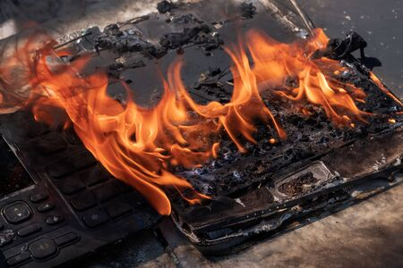 Fire in the office. Burnt laptop and phone. Loss of digital data. Business, property and accident insurance concept. Military action, sabotage, or deliberate destruction. Safety during the operation of electrical appliances. 版權商用圖片