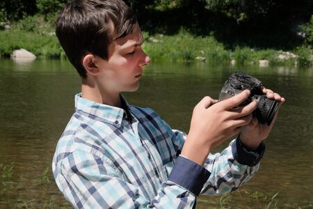 A teenager in a plaid shirt holds a molten camera in his hands. The guy looks sadly at the broken device. Heat on the river. The effects of fire.