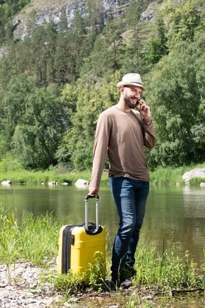 The guy in the hat is talking on the phone. Hipster young man hitchhiking along a mountain river with a yellow suitcase. Travel and vacation. Summer or tropics.