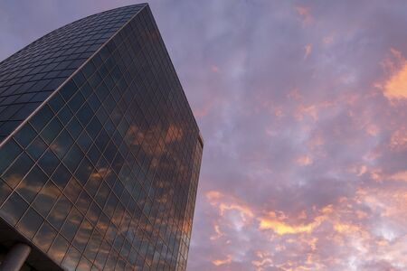 Modern glass high rise business building with reflected sunset in it. Evening red clouds. Copy space. Wallpaper. Great city view.