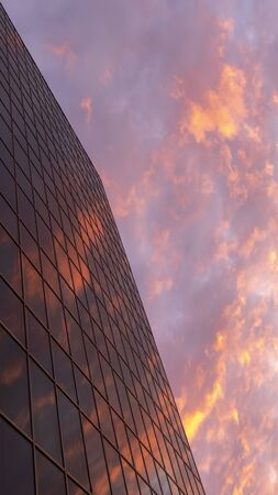 Abstract view of a skyscraper with a reflection of the evening sky and red clouds. Beautiful geometric city view. Vertical frame for Instagram stories. Copy space.