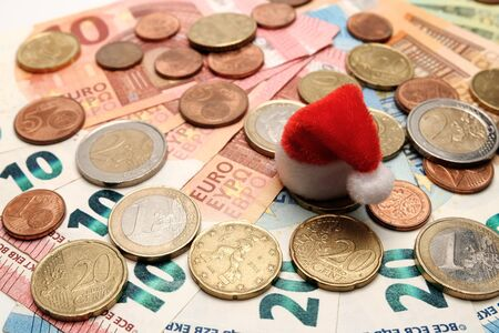Red santa claus hat on a background of euro coins and banknotes. The concept of New Year and Christmas spending and gifts. Background of european money.