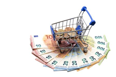 A stroller for shopping with coins stands on a fan of Euro banknotes. Banknotes 10,20,50,100 in the amount of 500 euros. How much European people spend money. The concept of a consumer basket in Europe, discounts, interest return. Template for black friday, cyber monday. Isolated.