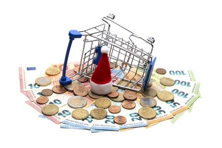 The stroller for shopping is tipped over on a fan of Euro banknotes and coins next to the Santa Claus hat. The concept of a consumer basket and spending money in Europe, the Christmas crisis, new year discounts, interest return. Isolated.