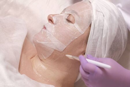 Anti-aging skin treatment. Cosmetology. The mask on the womans face. The girl in the beauty salon at the reception of a cosmetologist. Imagens