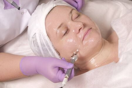 Transparent gel on a womans face. The electrode in the hand of a beautician in purple gloves. Hardware cosmetology. Anti-aging procedure for womens skin. Girl in a beauty salon.