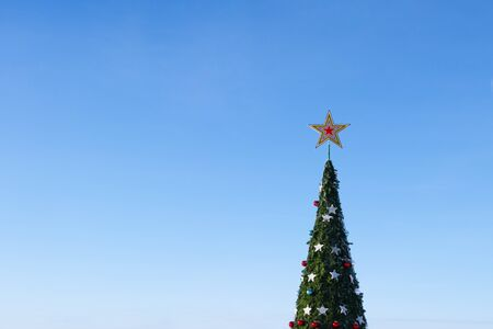 Christmas tree. The crown of a big New Year tree with a star and toys against a blue cloudless sky. Festive winter mood and holiday decoration. Copy space.