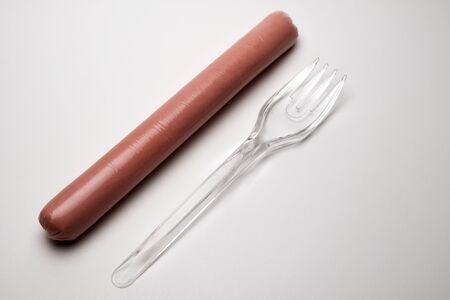 Sausage next to a plastic transparent fork on a white background. Copy space. The concept of fast food, GMOs, hunger or lack of food. Environmental issue and the ban on plastic dishes.