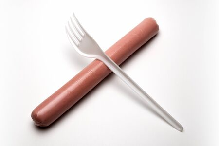 A plastic fork lies crosswise on a hot dog sausage. Ban plastic dishes. The concept of fast food, hunger or lack of food. Ecological problem, GMOs. White background. Copy space.