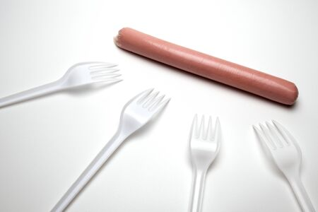 One sausage and four plastic forks on a white background. The concept of nutrition in a poor society. Environmental issue and the ban on plastic dishes. Hunger or lack of food. Copy space.