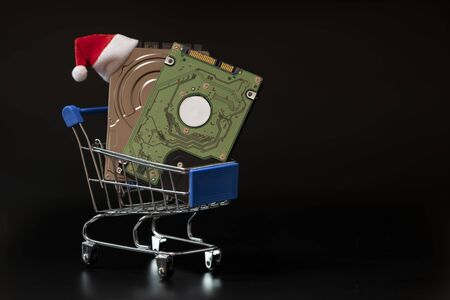 Two laptop hard drives and a red santa claus hat in a blue shopping basket. Black background. Christmas sale and discount concept, black friday, cyber monday. Copy space. Template for the design of an advertising banner.